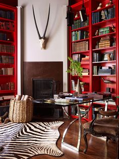 Home office filled with drama and lots of red: the zebra rug and amazing skull with horns stand out amidst the red bookshelves. Red Office, Office Decor, Home Office, Modern Interior Design, Interior Styling, Interior Decorating, Red Bookcase, Bookshelves, Home Libraries