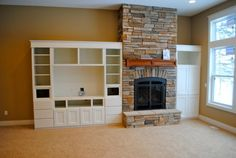 This brick fireplace with mantel is slightly raised off of the ground, creating a major focal point. Adjacent to the fireplace, is a custom-built entertainment center. Off Center Fireplace, Fireplace Tv Wall, Family Room Fireplace, Fireplace Bookshelves, Fireplace Furniture, Fireplace Ideas, Bookcases, Glass Tv Unit, Basement Remodeling