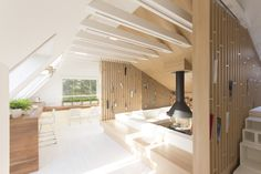 Renovated mansard styled attic with sofas arranged around the fireplace Moscow Russia [20001333]
