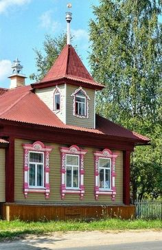 Russian wooden house with carved decorations and a birch tree nearby. #Russian #wooden #house