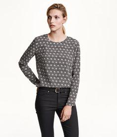 Een blouse van geweven kwaliteit met een licht onregelmatige structuur. De blouse heeft lange mouwen, een sluiting op de rug en een iets langer achterpand.