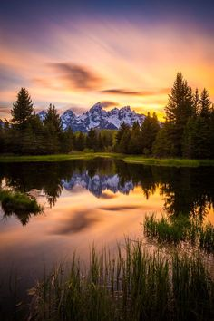 The sun sets over the iconic Grand Teton from Schwabacher's Landing in Grand Teton National Park, Wyoming.