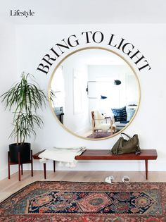 White entrance hall with dark wooden bench and carpet and large round mirror