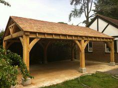 Green oak timber framed BBQ shelter for garden with cedar shingles