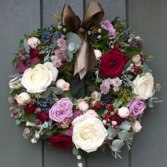 This woodland door wreath has a mixture of luxury scented red, cream & plum roses which are exclusively grown on our farm in Kenya. We have mixed these beautiful roses with Pussy Willow, plum Astrantia and blue Viburnum berries in this deluxe arrangement with seasonal winter foliage, all grown on our English Farm. AVAILABLE TO PRE ORDER FOR CHRISTMAS. FIRST DELIVERY DATE FOR THIS WREATH IS TUESDAY 2ND DECEMBER 2014!