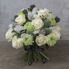 White Roeses,green pon pon ranunculus, berries, ivy, pine and frosted cones. Christmas-Bouquet-McQueens-Flowerona-2