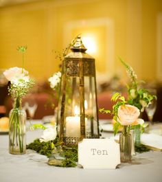rustic lanterns and bud vases.... we sub the bud vases for small cylinders with candles and vintage wine glasses with succulents.