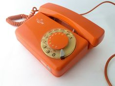 Vintage orange rotary telephone.
