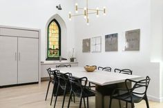 This modern white kitchen, dining area and living room combo from Linc Thelen features a tall gray fireplace as well as a large cathedral-style stained glass window in the kitchen.