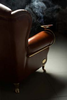 Cigar gallery. Nice leather chair, elegant cigar ashtray accessory. Totally man.