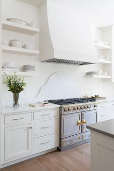 La Cornue CornuFe Range sits against a curved white marble backsplash and between white shaker cabinets adorned with nickel hardware and a white marble countertop.