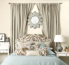 I think we should use our bed and create a focal point in our room using this very styling setup.  I am thinking of taking our patterned blue drapes since we really don't need them at the window and placing them behind our bed in this very fashion.  We already have a round mirror to place above (should we want a mirror above our bed).  We just NEED a headboard and new bedside stands and lamps.