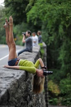 A dancer snaps a photo atop a ledge.