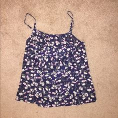Floral tank top Never worn but tag is off. Spaghetti strap floral tank top with Ruffles going down the front, although the you can't see it in the picture. It's navy with pink and white flowers. Macy's Tops Tank Tops