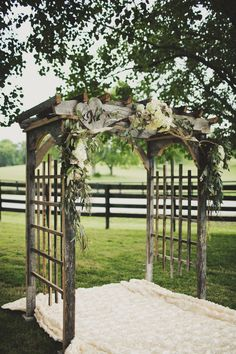 beautiful wooden wedding altar with lavender, rosemary, sage, thyme gathered at the top with white lace drape and sides
