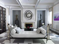A sleek sitting area by Jean-Louis Deniot embraces the color white and showcases modern art, placed in alcoves that flank the fireplace. | archdigest.com