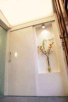Posuvné lakované dveře se skrytým mechanismem oddělují úzký prostor zádveří a šatny. Aby stěna vedle dveří v jejich zavřeném stavu nezůstala holá, designéři ji ozvláštnili mělkou nikou s osvětlením, zakázková výroba; Toto studio