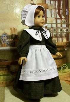 Pretty Pilgrim black ensemble. White wool stockings & brass buckle shoes. Full skirting, white lace apron.  Stand up collar, White collar with bow at center, long sleeves