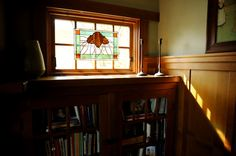 Light streams through a living room window where stained glass glows with a pinecone motif. Don and father Ray did all the woodwork themselves, including the paneling and built-in bookcases.