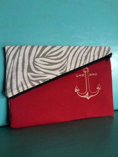 """★ ☆ Nautical Clutch ☆ ★<br/><br/>This handmade clutch is made with printed canvas and dark red and khaki cottons.<br/>A simple anchor is embroidered on the front for a classic look.<br/>This clutch has a magnetic snap closure on the flap, and a zipper closure to secure everything while you're out.<br/><br/>★Measurements★<br/><br/>9 1/4""""x6.5""""<br/><br/>★THIS ITEM IS READY TO SHIP.★<br/>THIS DESIGN IS A ONE OF A KIND.<br/><br/>★CARING FOR YOUR DESIGN★<br/><br/>Machine wash in COLD…"""