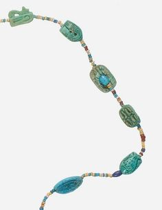 MET EGYPTIAN AMULET NECKLACE, NEW KINGDOM, DYNASTY 18, REIGN OF AMENHOTEP III C. 1390-1353 BC  Found in Amenhotep III's ancient palace complex at Malkata in Thebes during the excavations of 1910-11. Made of Faience and glazed steatite.  Amenhotep III's reign was a period of unprecedented prosperity and artistic splendor, when Egypt reached the peak of its artistic and international power. When he died in the 38th or 39th year of his reign, his son initially ruled as Amenhotep IV,