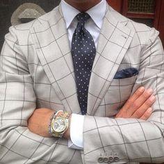 グレーチェック柄のスーツにネイビーの小紋タイを合わせた着こなし