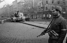 A Hungarian soldier, wearing an armband marking his defection to the anti-USSR insurgents, stands near a damaged Soviet tank in Budapest, late 1956 [[MORE]] Photo by Erich Lessing. World History, World War Ii, Isu 152, Best Armor, Photographer Portfolio, Cities In Europe, Magnum Photos, Budapest Hungary, Eastern Europe