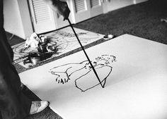David Hockney, drawing Celia Birtwell on a litho plate using a long stick, 1981. Photo by Sidney Felsen.