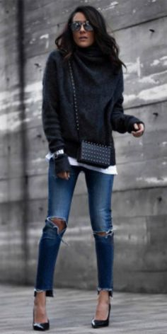 Lucy Hernandez + distressed denim jeans + patent navy stilettos + oversized dark grey turtleneck + cosy and comfortable spring outfit. Brands not specified.