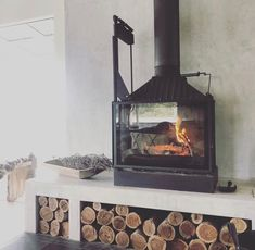 Modern fireplace, hearth design on raised bench with wood storage. Cheminees Philippe Radiante 747 dual opening slow com. Fireplace Hearth Stone, Wood Stove Hearth, Log Burner Fireplace, Tv Above Fireplace, Home Fireplace, Modern Fireplace, Fireplace Design, Freestanding Fireplace, Wood Storage