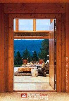 Gorgeous! Looking Through Front Entrance to Back Patio | Custom Timber Frame Home by PrecisionCraft Log Homes