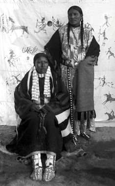 "Portrait of She Came Spotted and an unidentified Native American Sioux woman, posed outside on a fur skin rug in front of a painted backdrop of a Lakota style Indian war record, Pine Ridge Agency, South Dakota. Photo: ca. 1890. - One problem with this photograph is we're not told which one of the women is ""She Came Spotted"", at a guess I'll go for the lady seated. At least that's a 50% chance of being right! Love the painted backdrop. Wonderful."