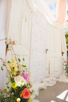 Old doors draped in lace as a backdrop for the ceremony