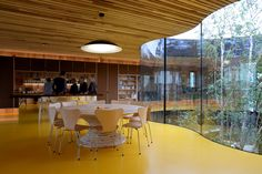 A courtyard with undulating glass walls descends from the base of the stilted wooden structure of this Maggie's Centre for cancer care in Oldham