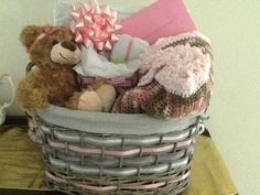 "This is a basket I did for a baby shower, it includes a mommy gift. The basket is woven with the nursery colors and I added a liner so it could be used in the nursery, I crocheted a pink camo infant/toddler blanket, trimmed in baby pink with a girly ruffle, it also has a framed sign that reads,""We made a wish and you came true"" I made that also, from a solid oak frame and added pink bows, a stork, balloons, welcome home, and some other embellishments. I bought a teddy bear and gave her a…"