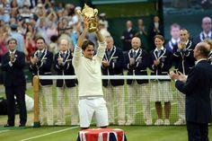 Roger Federer raises the championship trophy after winning his seventh Wimbledon title. - Matthias Hangst/AELTC