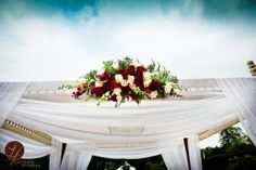 Gorgeous ceremony aisle arch - white sheer with red and white roses. Designed by Marrero Events