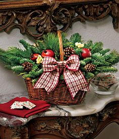 Country Christmas Basket....and it's easier than it looks. Wire a block of green foam in the bottom & add floral picks to the items ...or if you're going to disassemble it after the holidays, just lay them in the basket & add the bow, especially if it's not going to be moved.