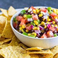 A photo of a white serving bowl of blackbean salsa surrounded by tortill chips. The salsa is filled with chunks of green bell peppers, fresh tomatoes, black beans, corn, and red onion.
