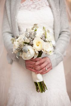 A white winter wedding bouquet with peonies, roses, duty miller, and silver brunia berries by Michelle Ferrara Handmade | Brides.com