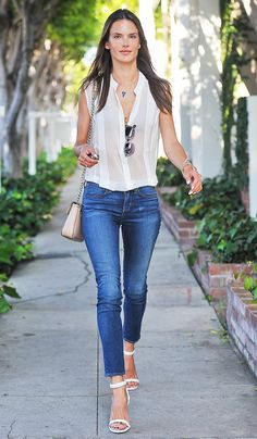 Alessandra Ambrosio in a white blouse,  jeans, and white strappy heels