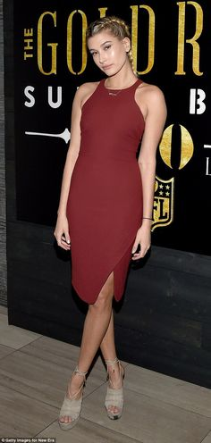 Burgundy beauty: The dress was sleeveless and fell to her knees, though a slight split on the left leg gave a hint of the beauty's lengthy gams
