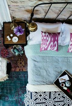 Ikat pillows and a Moroccan motif blanket add graphic interest and color to solid-color bedding, and the hues in the rugs in the background are perfectly saturated.