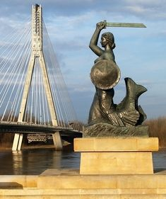 """Most Świętokrzyski, Pomnik Syrenki, Warszawa - The sculpture depicts the figure of Syrena with a raised sword and shield. On the shield there is an image of an eagle, around which the inscription """"Warsaw"""" runs Mermaid Sculpture, Mermaid Art, Paradise Places, Poland Travel, Central Europe, Krakow, Homeland, Places To See, Beautiful Places"""