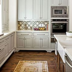 Custom cabinets in Sherwin-Williams' Mindful Gray and a showstopping tile backsplash raise the bar in this classic kitchen designed by Houston-based firm Chandos Interiors.  | Photo: Laurey W. Glenn