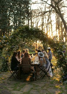 Magical dinner at sunset. Flower arches above tables for wedding.