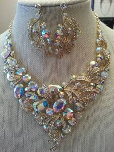 This is beautiful! Generous aurora borealis rhinestones are surrounded by swirls of pave rhinestones on gold tone florishes. This set reminds