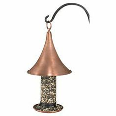 "Attract feathered visitors to your garden or backyard with this classic steel bird feeder, showcasing a turret-style roof and copper finish.  Product: Bird feederConstruction Material: SteelColor: CopperFeatures:  Turret style roofLipped feeding tray with drain holes prevents waste and keeps seed dryEasy to hang 3.5 lbs Seed capacityDimensions: 21.5"" H x 11"" DiameterNote: Easy assembly required"
