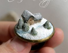 Miniature house is made out of polymer clay. Spruces, snowy landscape. Every detail is hand-sculpted with delicate instruments.  Diameter 25 mm. Adjustable size: 17 mm and more  Water-resistant  Delivery regular method (free shipping) takes about 3 weeks (sometimes up to 6 weeks) depending on your location.  Each purchase comes carefully packaged Please note that real colors may slightly differ from their appearance on your display