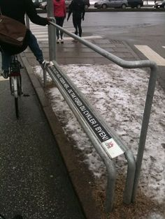 "A bike foot rest/railing in Copenhagen. The foot rest reads: ""Hi, cyclist! Rest your foot here... and thank you for cycling in the city."""